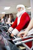 在踏车的圣诞老人锻炼 库存照片