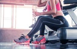 在踏车锻炼的妇女饮用水在健身健身房未被认出的面孔 库存照片
