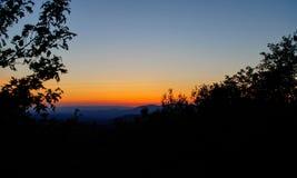 在蹦跳的人山的日落 库存图片