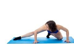 在蹲下的姿势的适合的女性模型 库存图片