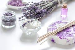 在身体的淡紫色草本关心与油的化妆用品在白色桌背景 免版税图库摄影