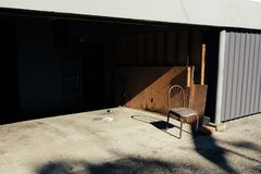 在车库前面的一把唯一椅子 免版税库存图片