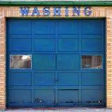 在车库海湾门的老洗车洗涤的标志 库存照片