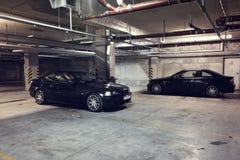 在车库的两辆黑汽车 免版税库存图片