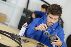 在车库的汽车修理师手与老引擎垫圈 免版税库存照片