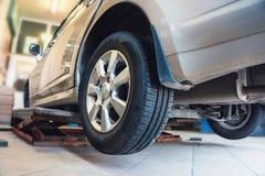在车库的汽车,汽车修理服务商店用特别修理的设备,变动轮胎和轮子概念 免版税库存图片