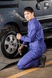 在车库的确信的技工定象车胎 免版税图库摄影