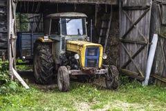 在车库里面的老黄色拖拉机 免版税库存照片