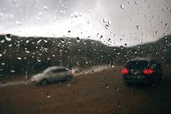 在车窗的灰色雨珠在一阴天 通过汽车汽车剪影的窗口外  免版税图库摄影