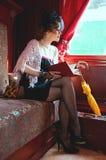 在车辆纵列的减速火箭的女孩阅读书。 免版税库存图片