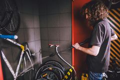 在车间为一辆自行车的专业洗涤物服务 有长的卷发的一个年轻白种人时髦的人做自行车clea 库存照片
