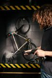 在车间为一辆自行车的专业洗涤物服务 有长的卷发的一个年轻白种人时髦的人做自行车clea 库存图片