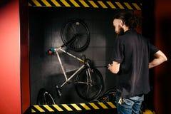 在车间为一辆自行车的专业洗涤物服务 有长的卷发的一个年轻白种人时髦的人做自行车clea 免版税库存图片