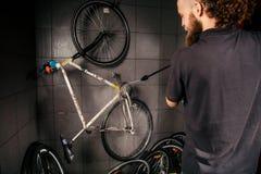 在车间为一辆自行车的专业洗涤物服务 有长的卷发的一个年轻白种人时髦的人做自行车clea 免版税库存照片