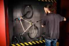 在车间为一辆自行车的专业洗涤物服务 有长的卷发的一个年轻白种人时髦的人做自行车clea 免版税图库摄影
