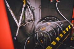 在车间为自行车服务专业洗涤物  手年轻白种人时髦的人特写镜头做自行车清洁usin的 库存图片