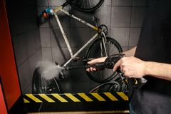 在车间为自行车服务专业洗涤物  手年轻白种人时髦的人特写镜头做自行车清洁usin的 免版税图库摄影
