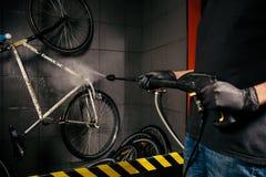 在车间为自行车服务专业洗涤物  手年轻白种人时髦的人特写镜头做自行车清洁usin的 图库摄影