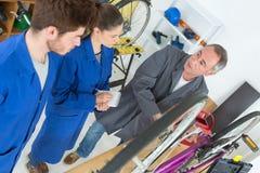 在车间骑自行车修理自行车的技工和学徒 免版税图库摄影