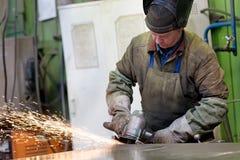 在车间的工厂焊工工作者研的钢片 免版税图库摄影
