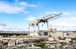 在轨道的巨型起重机使用重建雅典的Acroplis帕台农神庙有在前景组织的废墟的片断的 库存图片