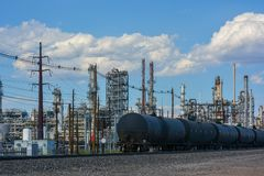 在轨道的油火车在精炼厂旁边 免版税库存照片