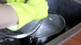 在转动在轻拍和洗涤平底锅的黄色橡胶手套的妇女的手与洗液和海绵 股票录像