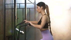 在转动的自行车的有吸引力的适合的妇女骑马在健身房 股票录像