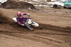 在转动的MX赛车手在含沙车轮痕迹 库存图片