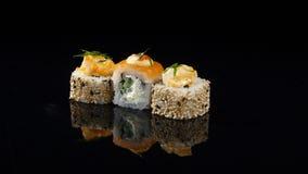 在转动黑的背景的三个不同寿司 库存照片