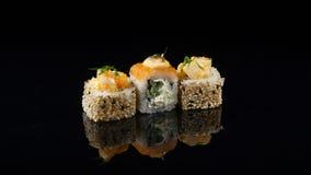 在转动黑的背景的三个不同寿司 免版税库存照片