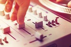 在转盘控制器的Dj使用的和混合的音乐 免版税库存图片