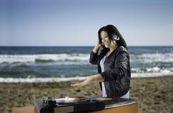 在转盘的妇女DJ混合的唱片 库存照片