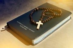 在转移光的一部黑皮革圣经的一个木花揪 免版税库存图片
