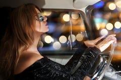 在轮子后的迷人的妇女在汽车 免版税库存图片