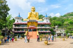 在轮子转动的姿势的大金黄菩萨雕象在Dambulla Golde 库存照片