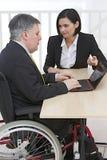 在轮椅的商人有助理的 免版税库存图片