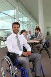 在轮椅的生意人 图库摄影