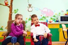 在轮椅的逗人喜爱的孩子在孩子的幼儿园有特别需要的 免版税库存照片