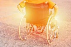 在轮椅轮子的人手在路的在城市公园使用我们保险耐心伤残概念图象温暖的口气 库存照片