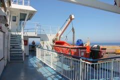 在轮渡船甲板的红色救生艇 免版税库存图片