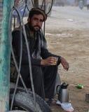在轮胎商店喝绿茶的一个人 免版税库存照片