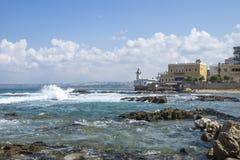在轮胎的海岸线在海洋有波浪的和有在轮胎,酸,黎巴嫩的灯塔的 库存照片