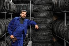 在轮胎附近的男性技工 免版税库存图片
