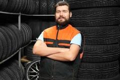 在轮胎附近的男性技工 免版税库存照片