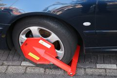 在轮胎附近的红色车轮固定夹在小室错误停放的汽车的Haag海牙在城市,首先将交罚款 库存图片