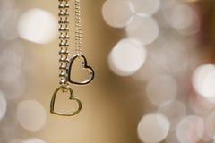 在软性隔绝的两条心脏垂饰项链弄脏了发光的背景 图库摄影