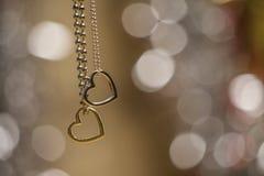 在软性隔绝的两条心脏垂饰项链弄脏了发光的背景 免版税库存图片