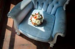 在软的古色古香的椅子的新娘花束 免版税库存照片