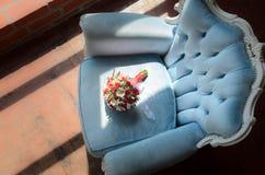 在软的古色古香的椅子的新娘花束 图库摄影
